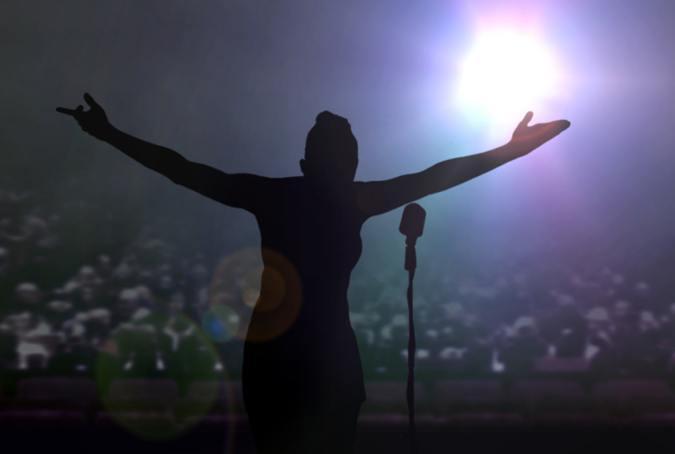 Eine Sängerin auf einer Bühne bedankt sich bei den Zuhörern