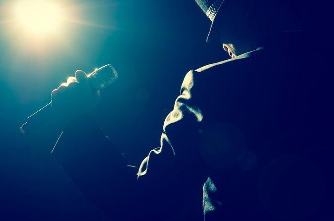Es ist ein Mann im Scheinwerferlicht zu sehen, der ein Mikrofon in der Hand hält