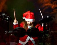 Mädchen mit Schlagzeug im Weihnachtsmannkostüm