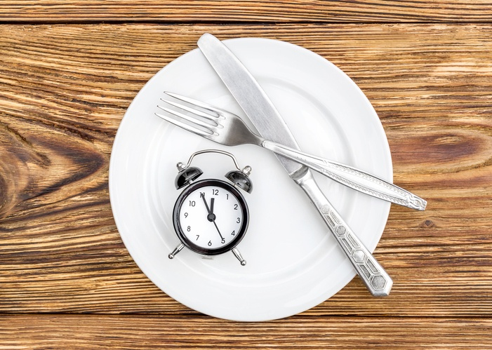 Wecker und Besteck liegen auf Teller