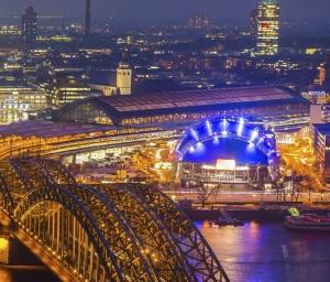 Die Kuppel des Musical Dome Köln leuchtet nachts blau.