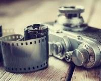Kamera und Film liegen auf einer hölzernen Fläche