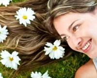 Frau mit lange blonden Haaren liegt mit dem Rücken im Gras und hat Blumen im Haar