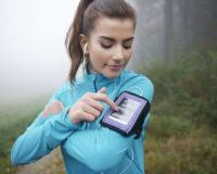 Junge Frau beim Joggen im Wald mit mobiler Fitness-App