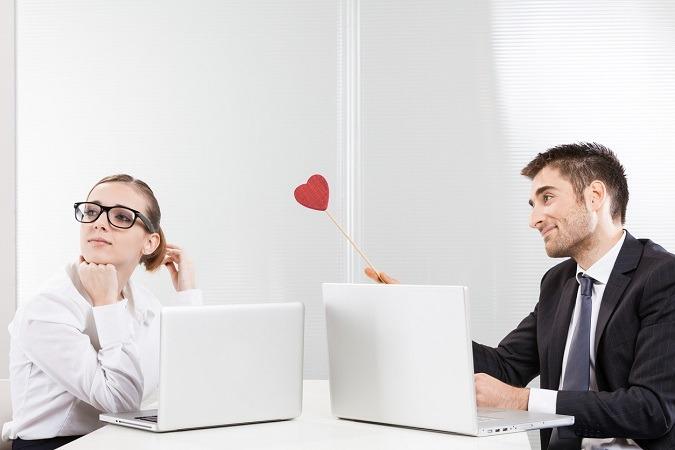 Mann und Frau sitzen vor Laptops. Er hält einen Herz-Lolli und guckt verliebt.